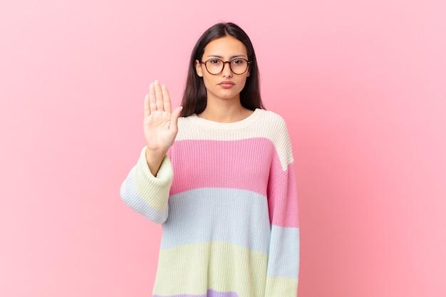 Latynoska ładna kobieta wygląda poważnie, pokazując otwartą dłoń, wykonując gest zatrzymania