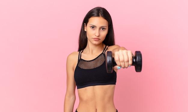 Latynoska ładna kobieta z hantlami. koncepcja fitness