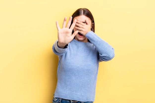 Latynoska ładna kobieta zakrywająca twarz dłonią i przykładająca drugą rękę do przodu, aby zatrzymać aparat, odmawiając robienia zdjęć lub zdjęć