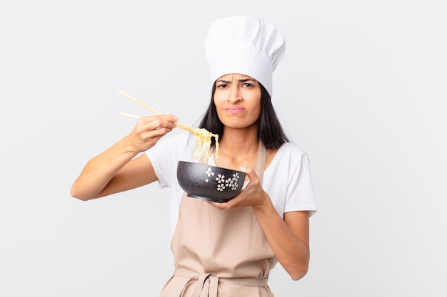 Latynoska ładna kucharz kobieta trzyma miskę z makaronem