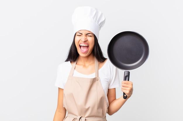 Latynoska ładna kucharz kobieta trzyma patelnię