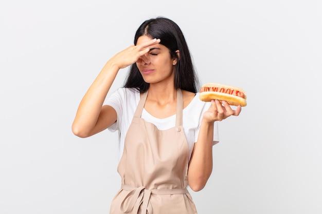 Latynoska ładna kucharz kobieta trzymająca hot doga