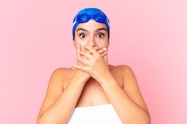 Latynoska ładna pływaczka zakrywająca usta dłońmi zszokowana goglami