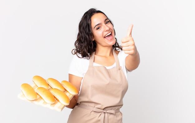 Latynoska ładna szefowa kuchni czuje się dumna, uśmiecha się pozytywnie z kciukami do góry i trzyma bułeczki troy