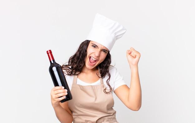 Latynoska ładna szefowa kuchni krzyczy agresywnie z gniewnym wyrazem twarzy i trzyma butelkę wina