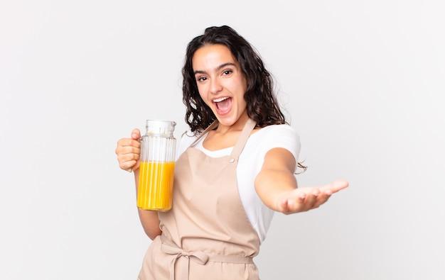 Latynoska ładna szefowa kuchni przygotowuje sok pomarańczowy