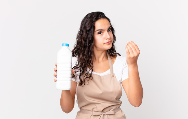 Latynoska ładna szefowa kuchni robi gest kaprysu lub pieniędzy, każe ci zapłacić i trzyma butelkę mleka