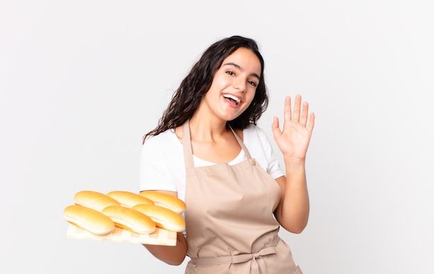 Latynoska ładna szefowa kuchni uśmiecha się radośnie, macha ręką, wita cię i wita i trzyma troję z bułkami