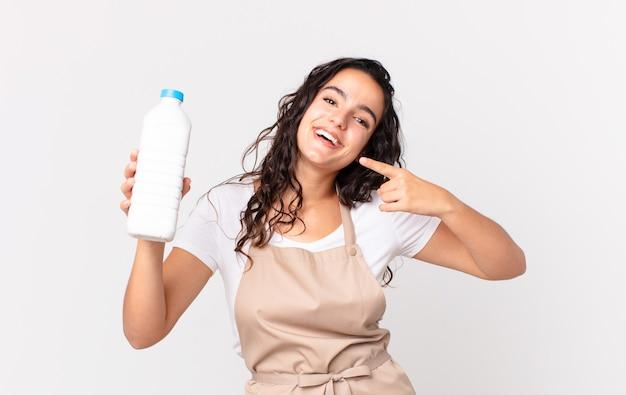 Latynoska ładna szefowa kuchni uśmiechnięta pewnie, wskazująca na swój szeroki uśmiech i trzymająca butelkę mleka