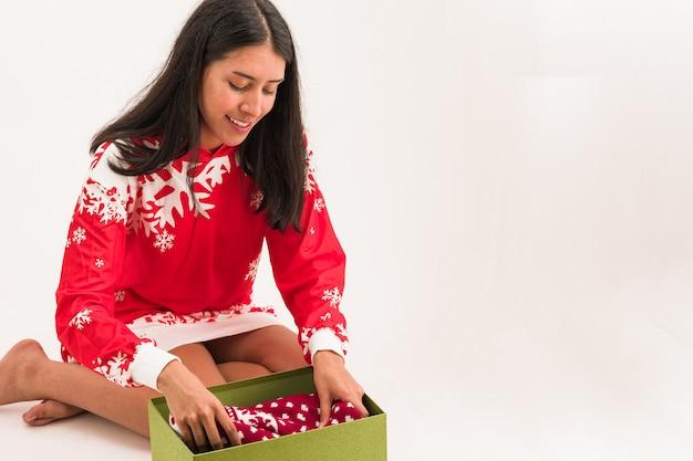 Latynoska otwiera pudełko na prezenty świąteczne brzydki sweter prezent świętujący boże narodzenie