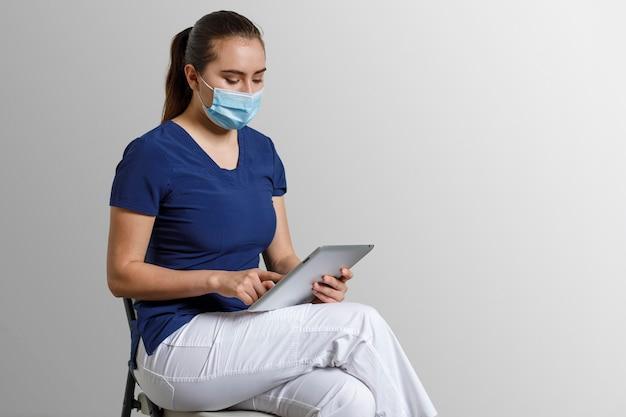 Latynoska pielęgniarka z maską siedząca pracująca z cyfrowym tabletem