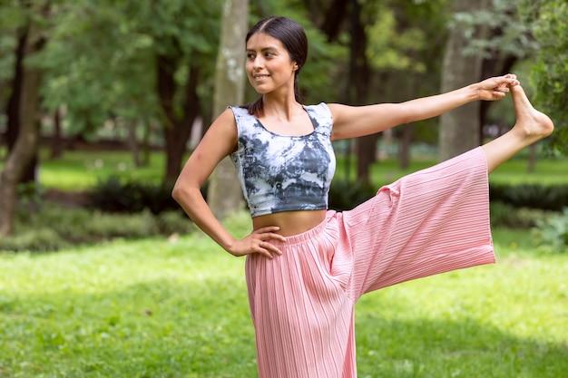 Latynoska robi pozy jogi, chwytając stopę w parku na zielonej trawie w różowym stroju