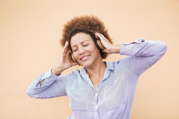 Latynoska starsza kobieta tańczy podczas słuchania playlisty muzycznej
