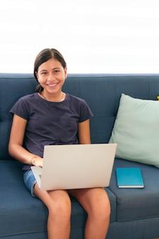Latynoska studentka śmiejąca się z laptopem w domu
