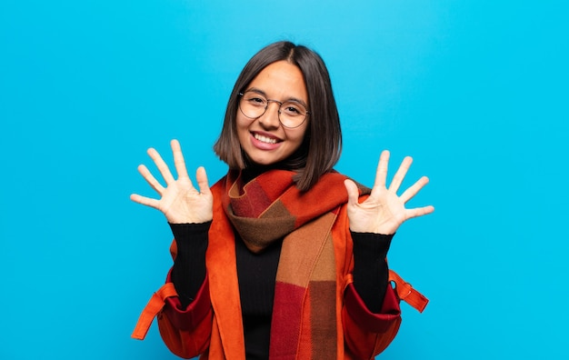 Latynoska uśmiechnięta i wyglądająca przyjaźnie, pokazująca cyfrę dziesiątą lub dziesiątą z ręką do przodu, odliczając w dół
