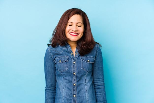 Latynoska w średnim wieku odizolowana na niebieskim tle, śmieje się i zamyka oczy, czuje się zrelaksowana i szczęśliwa.