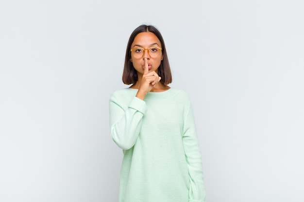 Latynoska wyglądająca poważnie i krzywo, z palcem przyciśniętym do ust, domagająca się ciszy lub spokoju, zachowywania tajemnicy