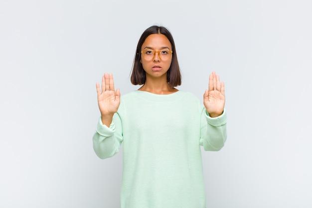 Latynoska wyglądająca poważnie, niezadowolona, zła i niezadowolona, zakazująca wejścia lub mówiąca stop z otwartymi dłońmi