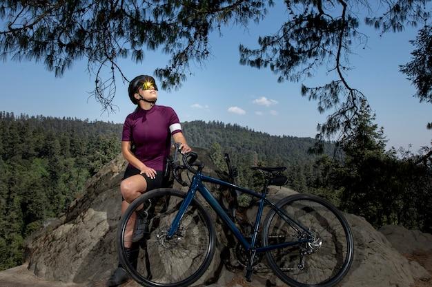 Latynoska z rowerem odpoczywa w lesie z pejzażem drzew w tle