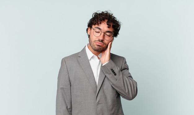Latynoski biznesmen czuje się znudzony, sfrustrowany i senny po męczącym, nudnym i żmudnym zadaniu, trzymając twarz dłonią