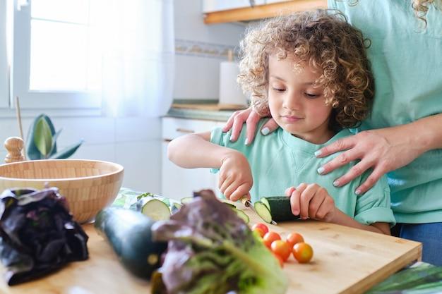 Latynoski chłopiec kroi nożem plastry ogórka w kuchni pod okiem mamy.