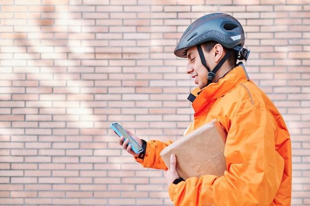 Latynoski kierowca dostawy do domu sprawdza w telefonie komórkowym trasę doręczenia przesyłki