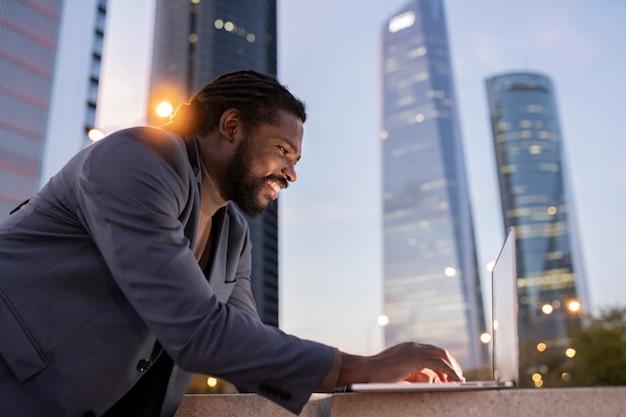 Latynoski latynos, biznesmen korzystający z laptopa w nocy, budynki w tle