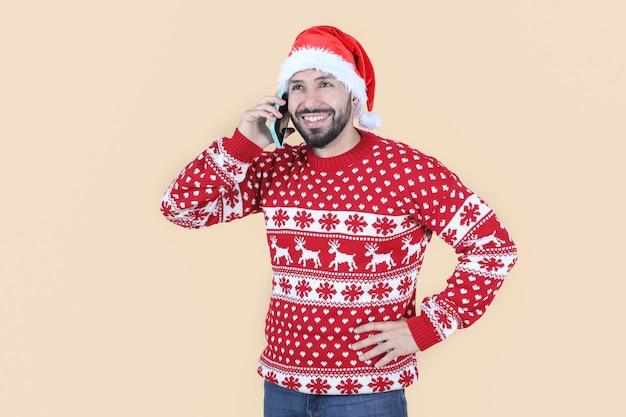Latynoski latynoski mężczyzna w świątecznym kapeluszu przy użyciu telefonu komórkowego