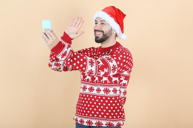Latynoski mężczyzna latynoski, w świątecznym kapeluszu, rozmowa wideo przez telefon komórkowy