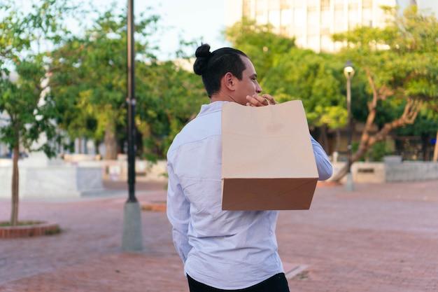 Latynoski mężczyzna na plecach z papierowymi torbami na zakupy na świeżym powietrzu
