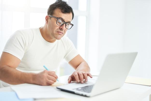 Latynoski mężczyzna w białej koszulce i okularach, patrząc skupiony, siedząc przy stole, używając laptopa i robiąc notatki. jasne światło wpadające z okna. biznesmen pracujący w domu podczas blokady