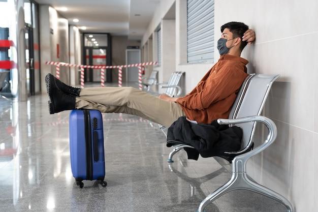 Latynoski mężczyzna z walizką spoczywającą na ławkach dworcowych