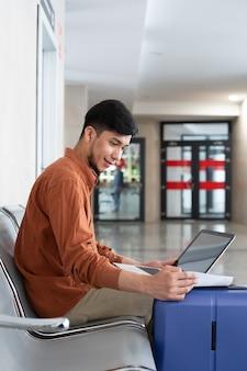 Latynoski siedzący na stacji z walizką i pracujący z laptopem