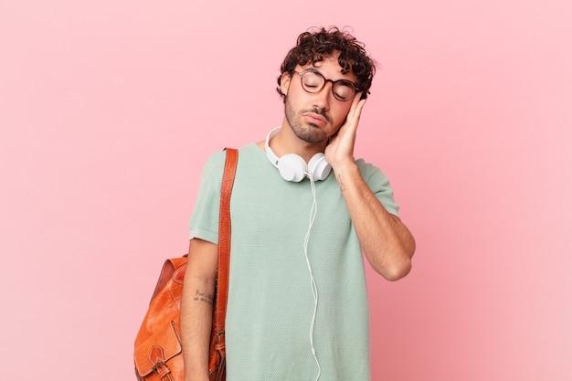 Latynoski student czuje się znudzony, sfrustrowany i senny po męczącym, nudnym i żmudnym zadaniu, trzymając twarz ręką