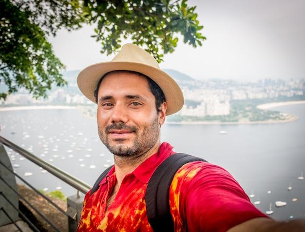 Latynoski turysta w kapeluszu w rio de janeiro na głowie cukru robi selfie i uśmiecha się wesoło w czerwonej koszulce
