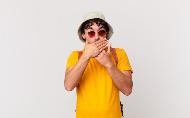 """Latynoski turysta zakrywający usta rękami z zszokowanym, zaskoczonym wyrazem twarzy, dochowujący tajemnicy lub mówiąc """"ups"""""""
