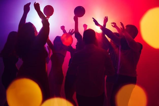 Lauder tłum ludzi w sylwetce podnosi ręce na parkiecie na neonowym świetle