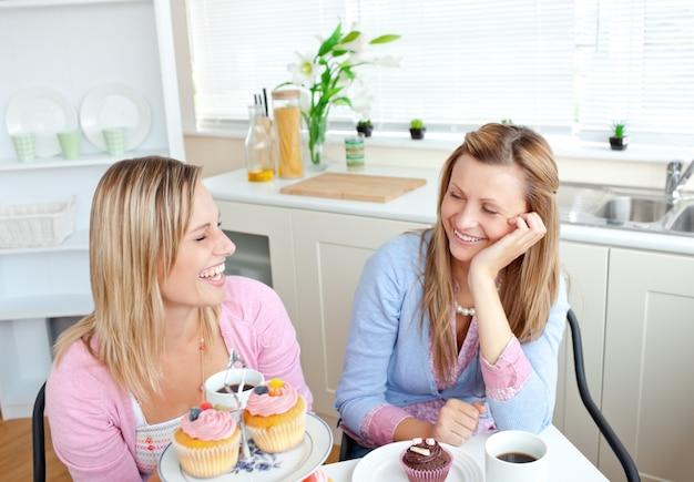 Laughing Kobiety Jedzenia Cupcakes I Picia Kawy Siedzi W Kuchni Premium Zdjęcia