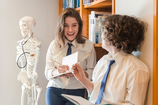 Laughing nastolatków robienia notatek w bibliotece
