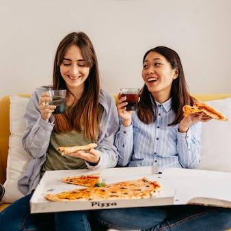 Laughing relaksujące dziewczyny korzystających z pizzy