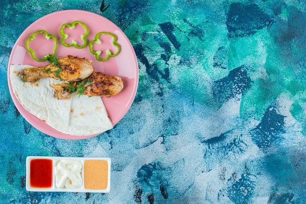 Lawasz, podudzia pieczone i pieprz na talerzu obok misek sosu z bliska, na niebieskim tle.