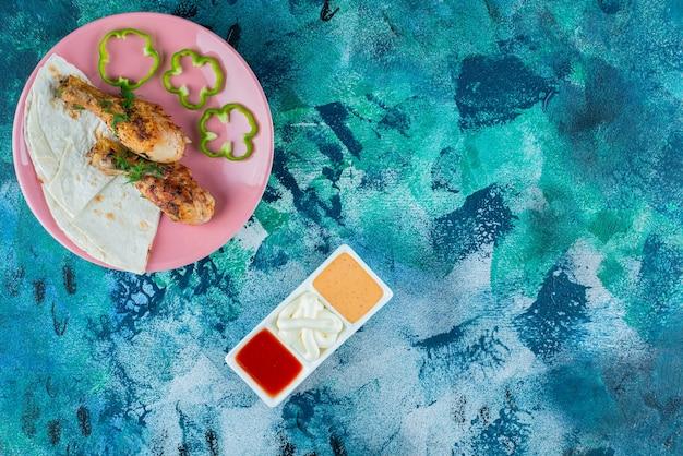 Lawasz, podudzia pieczone i pieprz na talerzu obok misek z sosem, na niebieskim tle.