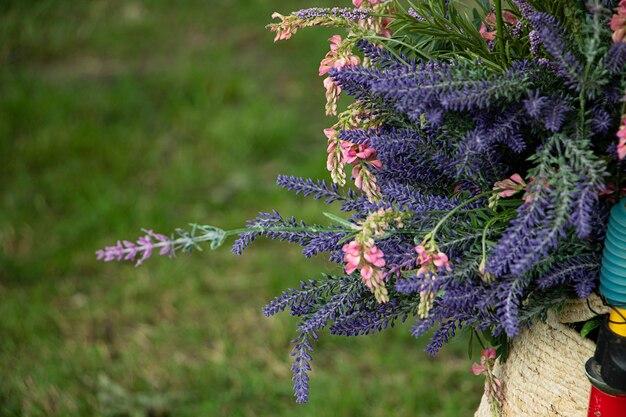 Lawenda i dzikie różowe kwiaty w wiklinowym koszu. koncepcja dekoracji letnich.