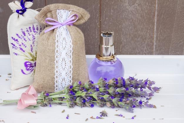 Lawendowa woda ziołowa w szklanej butelce, świeże kwiaty i susz w woreczku