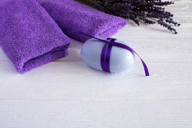 Lawendowe mydło i fioletowe ręczniki na białym tle