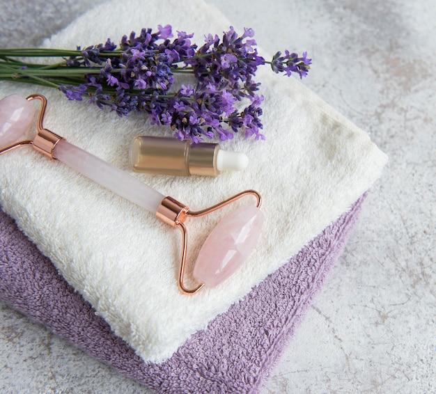 Lawendowe spa. olejki eteryczne, wałek do twarzy, ręczniki. naturalny kosmetyk ziołowy z kwiatami lawendy