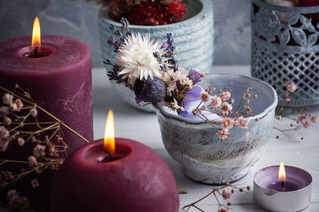 Lawendowy bukiet suchych kwiatów w wazonie na białym drewnianym stole i zapalonych świec. na powitanie, zaproszenie, kartki urodzinowe