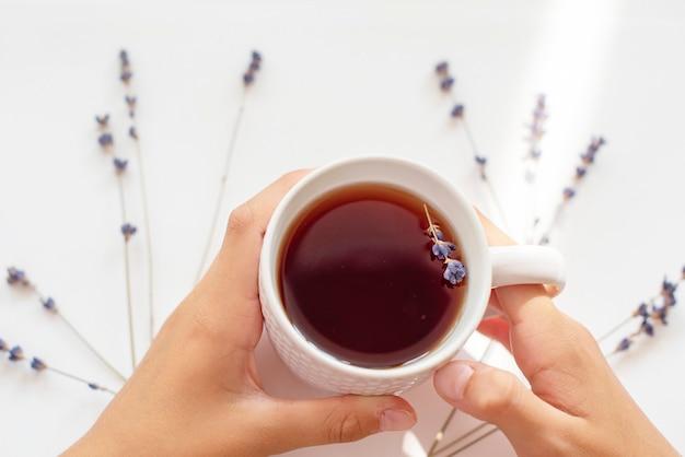 Lawendowy kubek herbaty w rękach