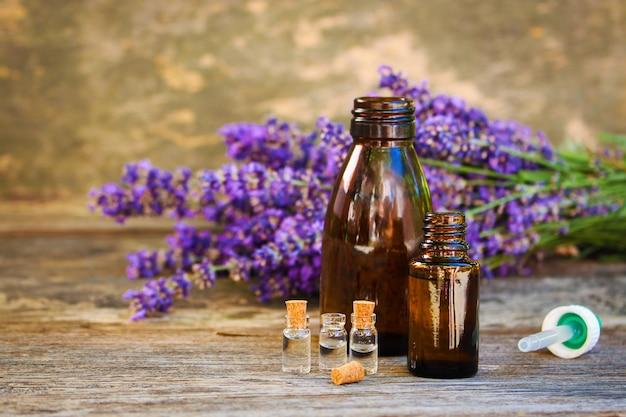 Lawendowy olej w różnych butelkach na drewnianym tle.