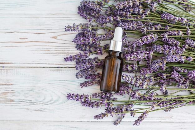 Lawendowy olej ziołowy i lawendowe kwiaty na szarym drewnianym